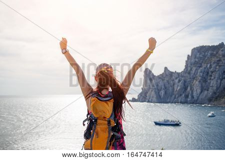 Young woman with raised arms on hill overlooking sea and mountains