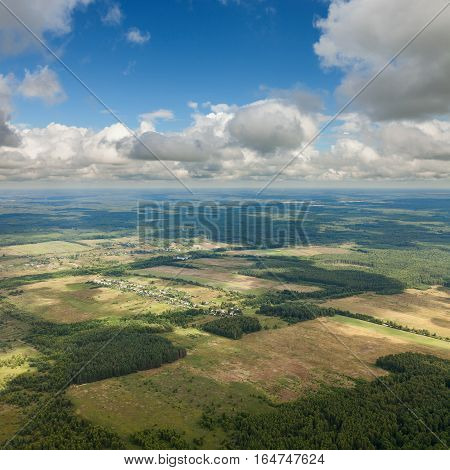 Aerial view of the countryside with fields of crops and pine forests in summer.