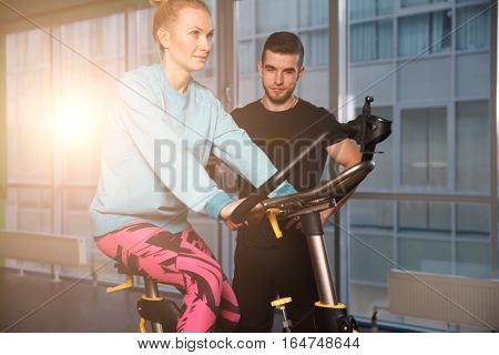 Trainer instructs woman on simulator in gym