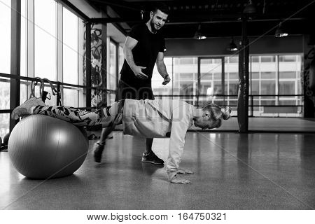 Black-white photo of girl on fitball at gym with trainer