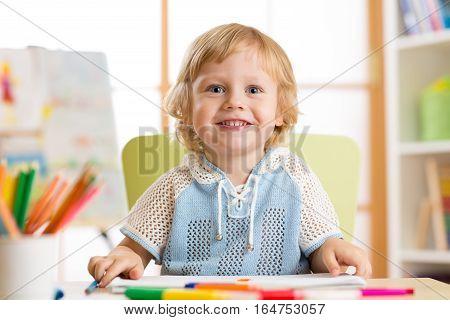 cute little boy drawing with felt-tip pen in kindergarten classroom