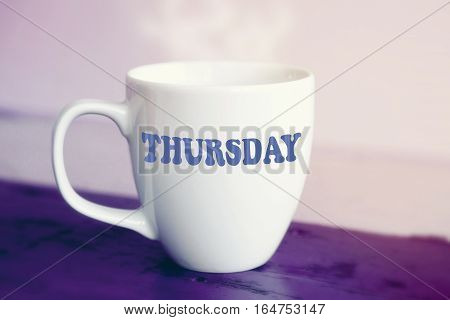 white cup with the word Thursday on it on purple wooden table