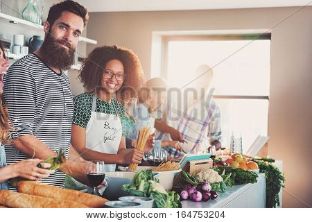 Two people from group of friends smiling at camera while cooking dinner together in light modern kitchen.