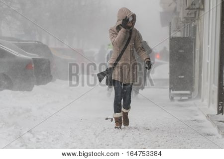 Bucharest Romania January 25 2014: A woman walks on the street during a blizzard in Bucharest.