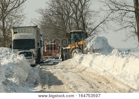 Bucharest Romania January 28 2012: A road sweeping vehicle clears snow from a road outskirts Bucharest.
