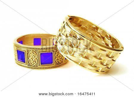 Close-up of golden bracelets isolated on white background