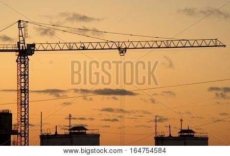 Silhouette of hoisting tower crane and the contours in house construction process on sunset view