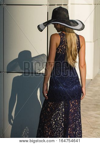 Young woman in black lace dress and hat with a wide brim. She stands back and her figure it casts shadow on wall of building.