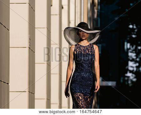 Young woman in black lace dress and a hat with a wide brim. She walks down street along building.