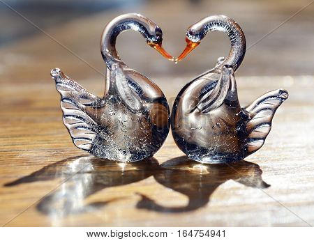 Two glass swans with necks forming a love heart shape.Figurine glass swans on wooden background.Saint Valentine background with two swans in love.Valentines day or love concept.Soft selective focus.