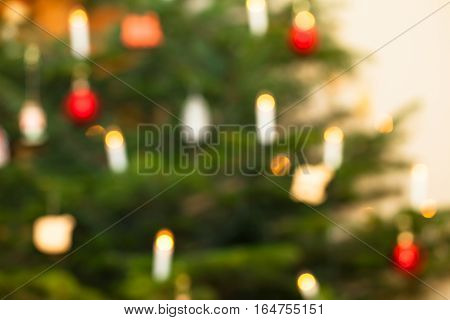 Defocused background of christmas tree with illuminated candles