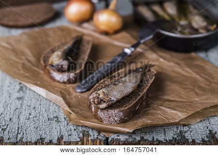 Smoked sprats with rye bread on wooden background