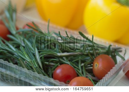 Fresh green rosemary red cherry tomatoes in a plastic food container and yellow capsicum