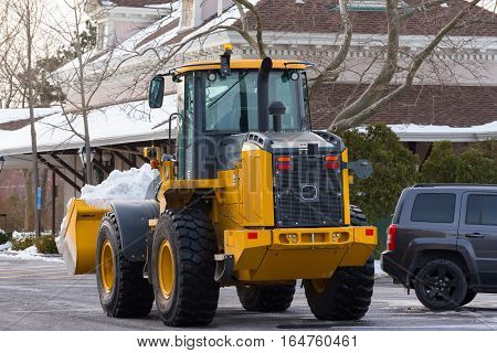 Spring Lake NJ USA -- January 10 2017. Editorial and Illustrative--Truck operator with a snowplow removes snow from a train station parking lot after a heavy snowfall.