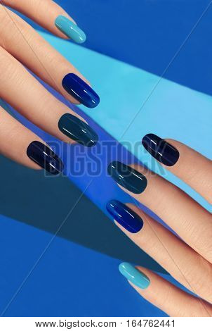Manicure with different shades of blue from light to dark on oval-shaped nails.