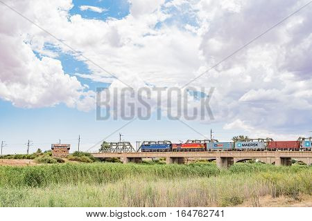 MODDERRIVIER SOUTH AFRICA - DECEMBER 25 2016: A train crossing the Riet River at Modderrivier. The Blockhouse used by British soldiers to defend the bridge during the second Boer War is visible