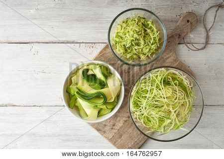 Raw zucchini noodles on the white wooden table top view