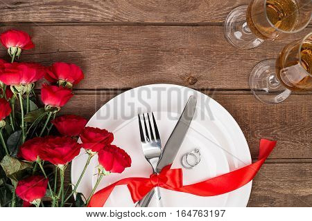 Valentine's Day dinner table setting with red ribbon, roses, knife and fork and ring over oak background. Still life