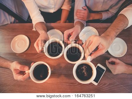 Top view of business people holding cups of coffee while having coffee break in cafe