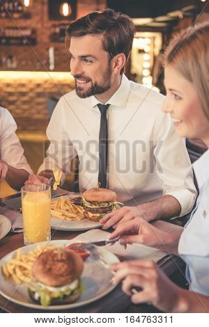 Business people are eating talking and smiling while having lunch in cafe
