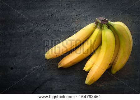 Bunch of bananas on the dark scratched table top view
