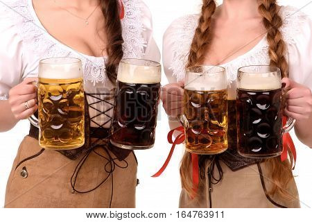 Two young sexy woman wearing a dirndl with beer mugs over white, Oktoberfest concept.