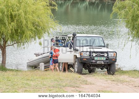 RITCHIE SOUTH AFRICA - DECEMBER 30 2016: Unidentified holidaymakers launching a boat onto the Riet River (reed river) at Ritchie a small town in the Northern Cape Province