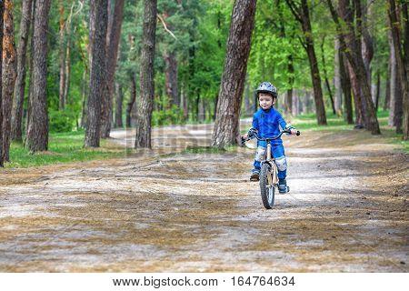 Happy Cute Blond Kid Boy Having Fun His First Bike On Sunny Summer Day, Outdoors.  Child Making Spor