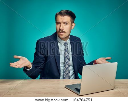 Sad Young Man Working On Laptop At Desk