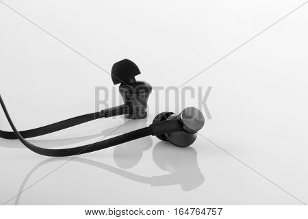 Stylish Black Earphones on White Reflective Background