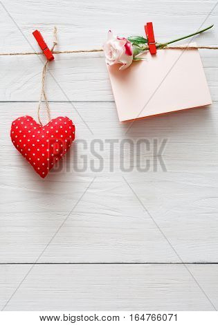 Valentine background with red pillow sewed heart on clothespins and paper card with rose flower on rustic wood planks. Happy lovers day mockup, copy space