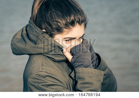 Outdoor portrait of a teenage girl wearing khaki parka with the hood on. Toned effect