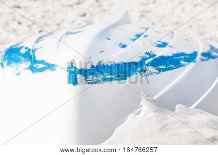 White row boat with blue stripe down in the beach sand