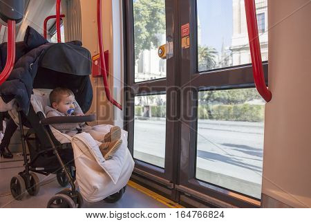 Baby boy having fun during a ride at streetcar Spain. He is sitting on his buggy