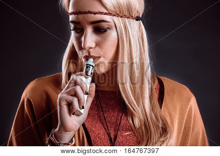 Young woman in the Boho style blowing smoke. The blonde on a dark background. Close-up
