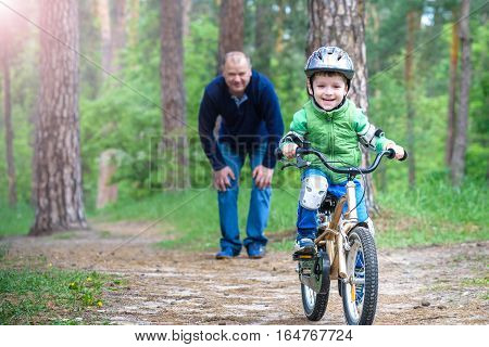 Little Kid Boy Of 3 Years And His Father In Autumn Forest With A Bicycle. Dad Teaching  Son. Man Hap