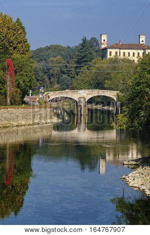 Old bridge over the Naviglio Grande of Turbigo (Milan Lombardy Italy) at fall. Fisheye