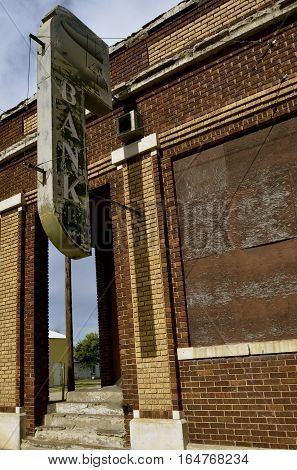 An old sign in a small town indicates the building was once a local bank