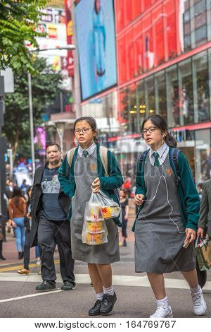 Hong Kong, China - December 6, 2016: typical asian school girls with clever look, carring food bag down the crowded street market Jardine's Crescent, Causaway Bay popular shopping district.