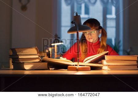girl reading a book in the library under the lamp.