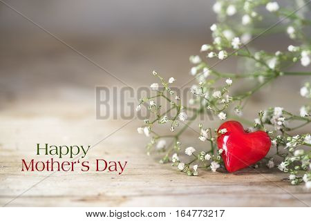 Small red heart from glass and white flowers on a rustic wooden background love concept sample text Happy Mother's Day selected soft focus very narrow depth of field