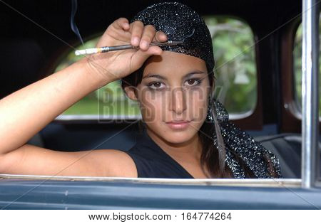 Beautiful gypsy woman sitting in an old car