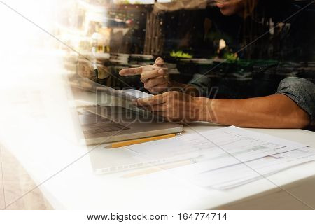 Asian business man manager analyzing datum in charts and typing on computer making notes in documents on the table in office vintage color selective focus. Business concept.