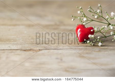 Small red heart from glass and white flowers on a rustic wooden background with generous copy space love concept for mother's day and valentine's day selected soft focus narrow depth of field
