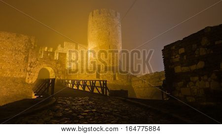 Tower and wooden bridge of Kalemegdan fortress at foggy night in Belgrade, Serbia