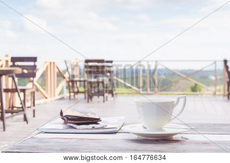 Cup of coffee on table on coffee-cafe on mountain landscape background