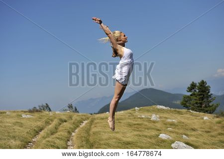 Purity of the human soul. Beautiful woman in white dress jumping in nature. She is free and happy.