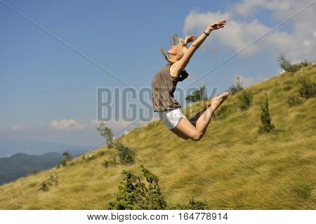 Beautiful young woman jumping for freedom. She is flying in the air. she was jumping on trampoline