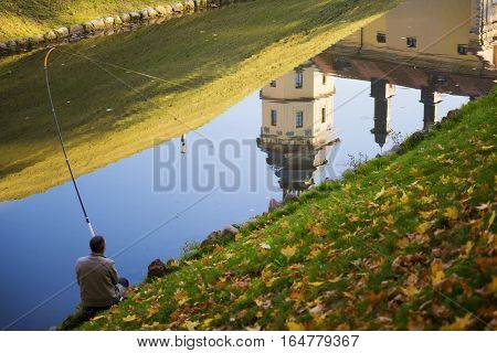 unidentified man fishing in water channel with medieval castle reflection