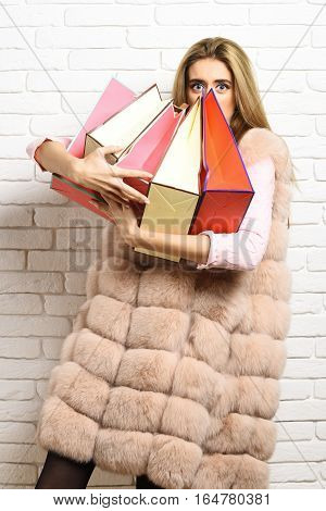 young fashionable sexy pretty woman or girl with long beautiful blonde hair in waist coat of beige fur and fashion makeup holding colorful package on brick wall studio background